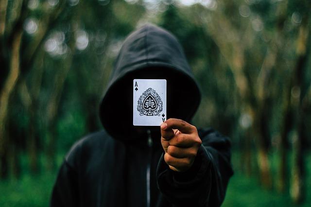 tajemný muž držící kartu před kamerou